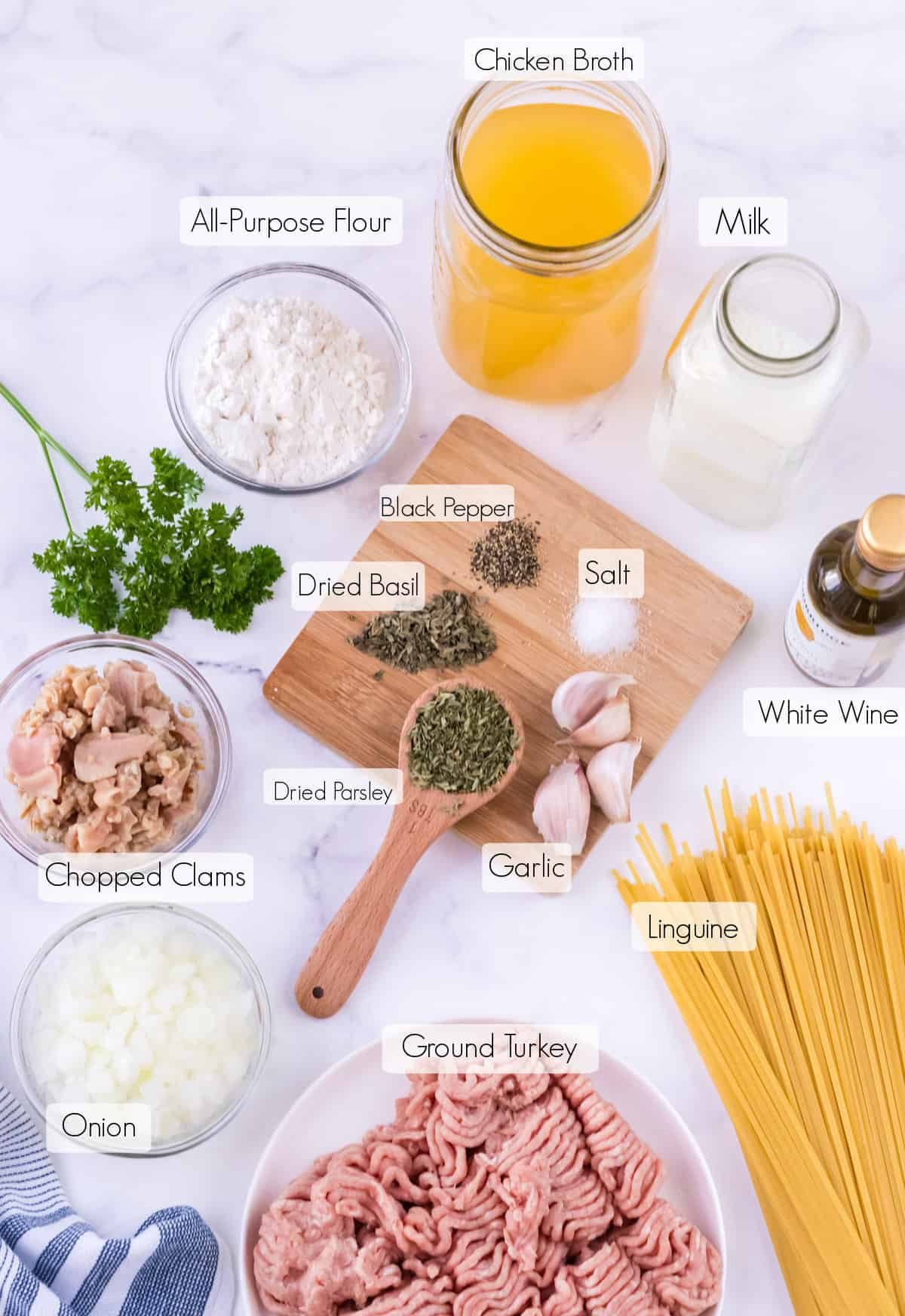 Labeled ingredients to make ground turkey and creamy clam sauce with linguine.