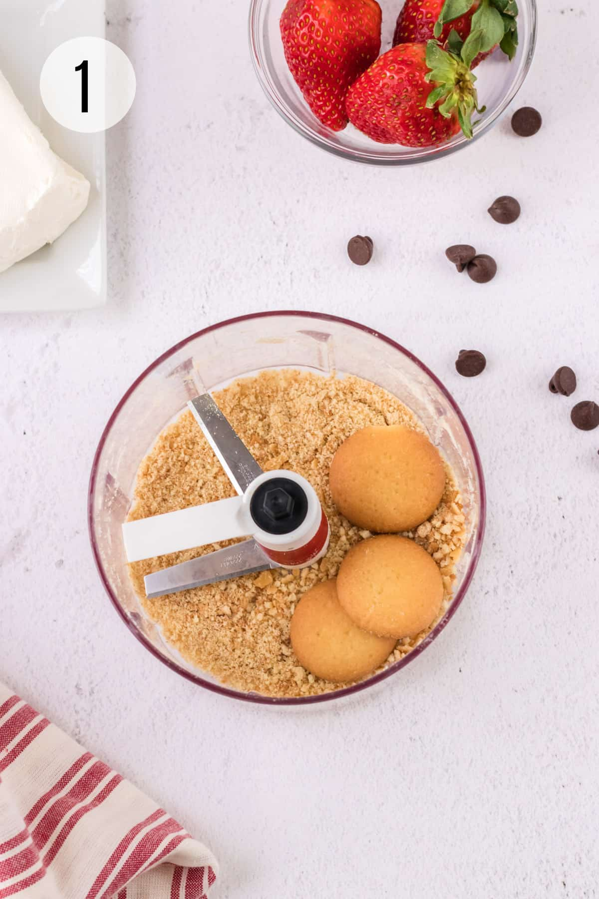 Handheld food chopper with vanilla wafer cookies finely chopped and chocolate chips, strawberries and cream cheese in upper background.