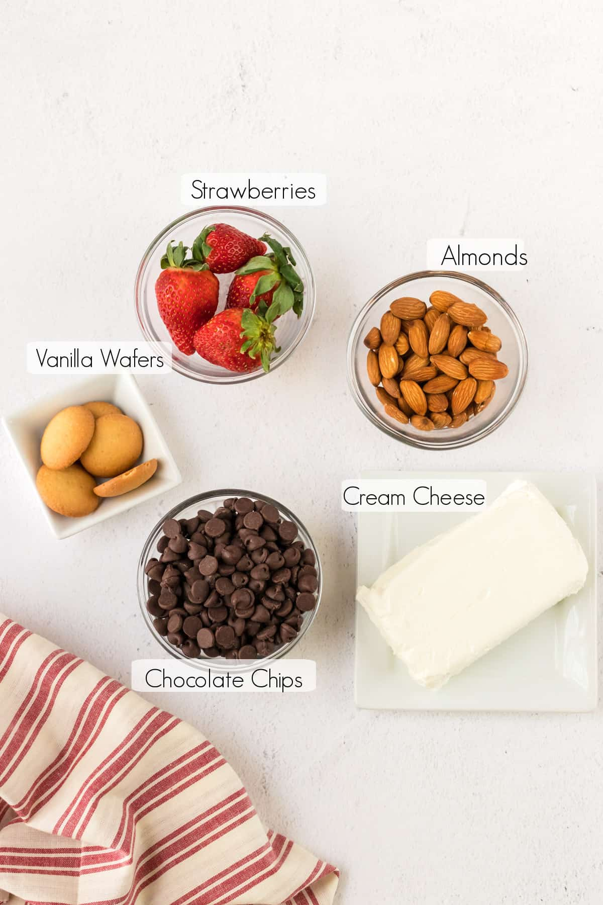 Labeled ingredients to make Strawberry Chocolate Cheesecake Bites with red and white linen in lower left corner.