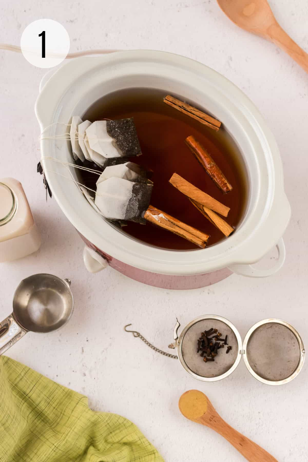 Slow cooker with tea bags and cinnamon sticks with mesh tea ball of cloves in lower right right and measuring cup and milk to left.