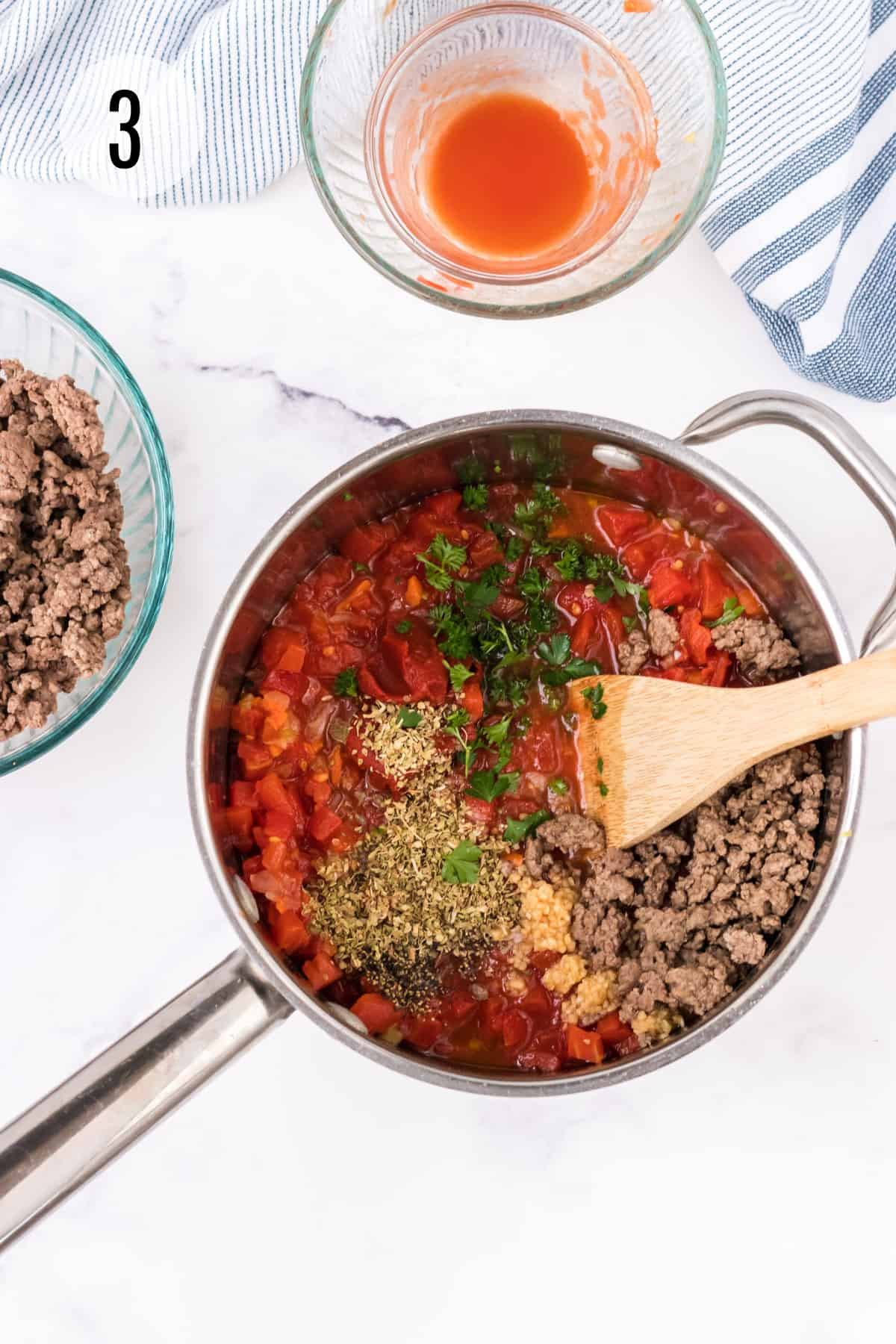 Saucepan with ingredients for homemade spaghetti meat sauce with herbs, ground beef and parsley with extra ingredient bowls in background with blue and white towel.