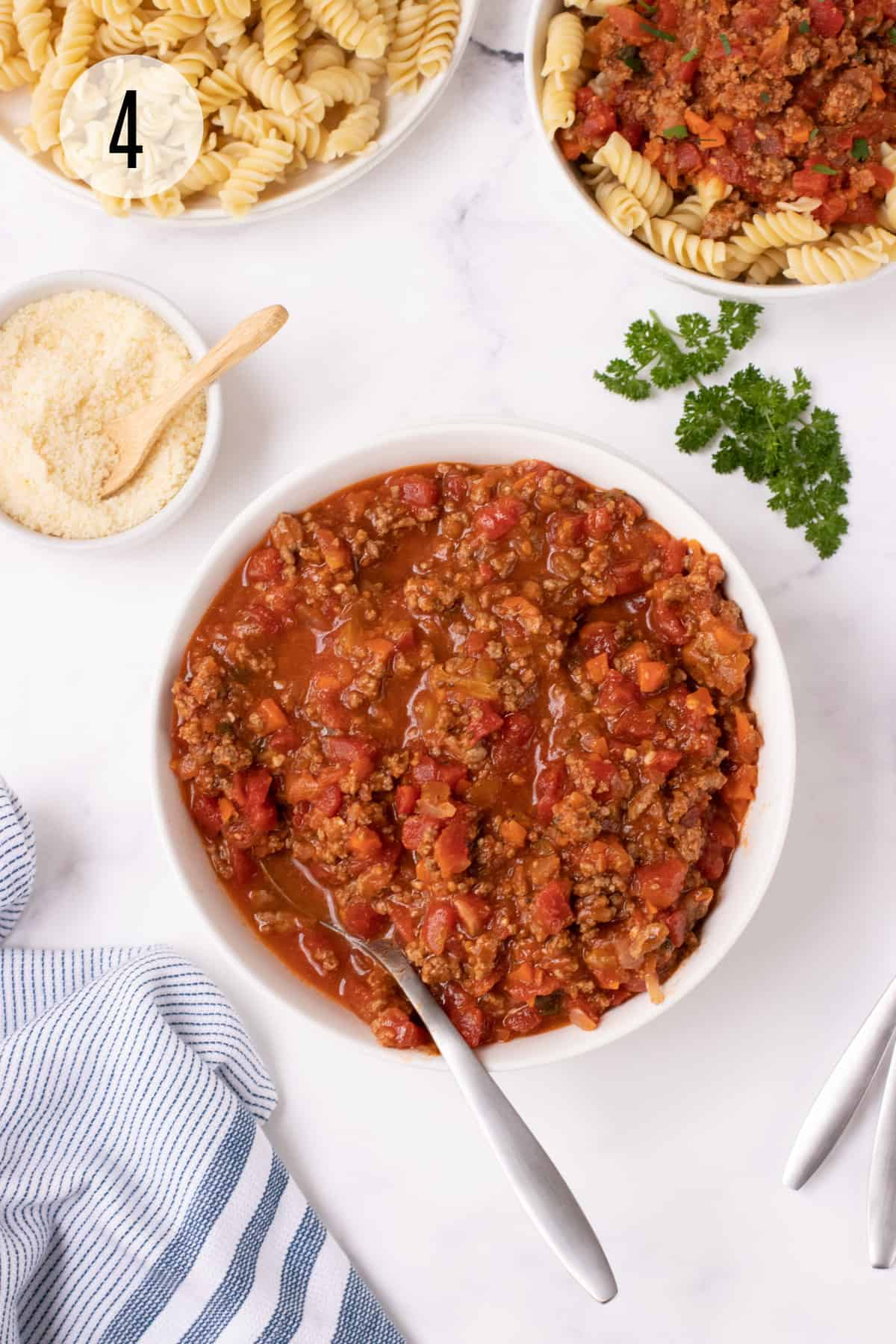 Bowl of chunky spaghetti meat sauce surrounded by fresh parsley and bowls of grated Parmesan, fusilli pasta and pasta with sauce and blue & white towel in lower left.