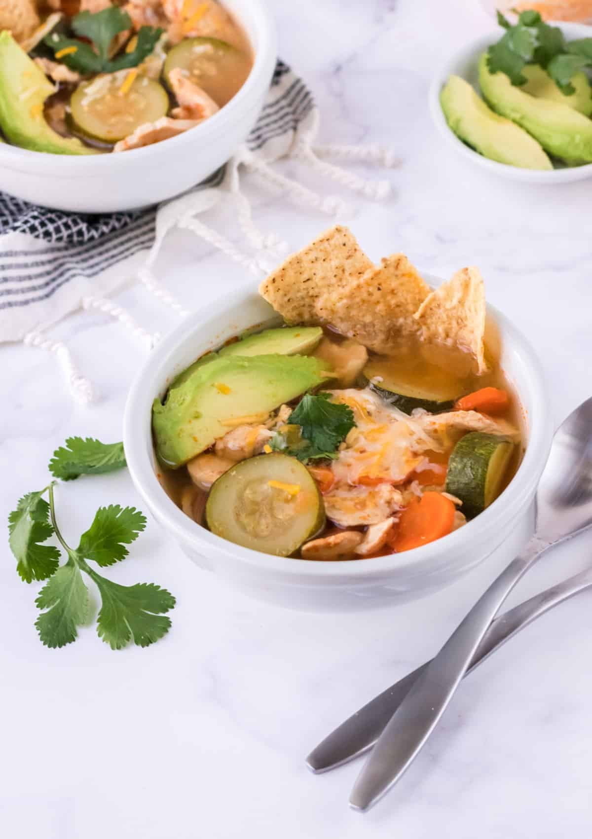 Bowl of chicken and vegetable tortilla soup with extra bowl in upper left and bowl of sliced avocados in upper right.