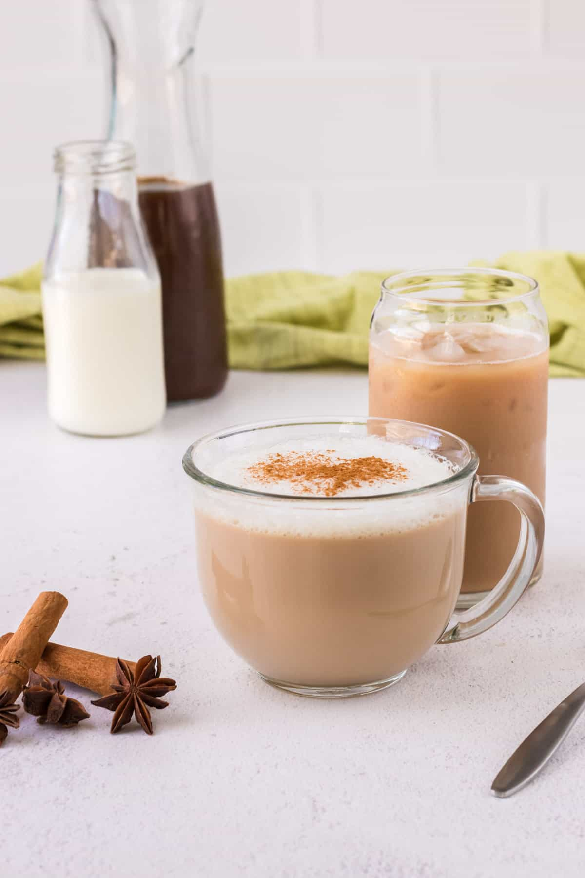 Glass mug with warm chai latte, taller glass with iced chai latte and milk and chai concentrate in background with cinnamon sticks and star anise in foreground.