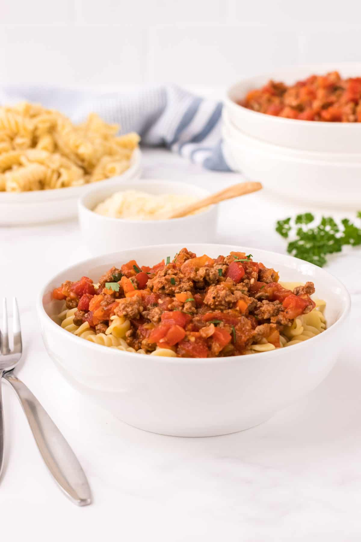 White bowl of chunky spaghetti meat and vegetable sauce with bowls of pasta, grated parmesan, more sauce and parsley in background.