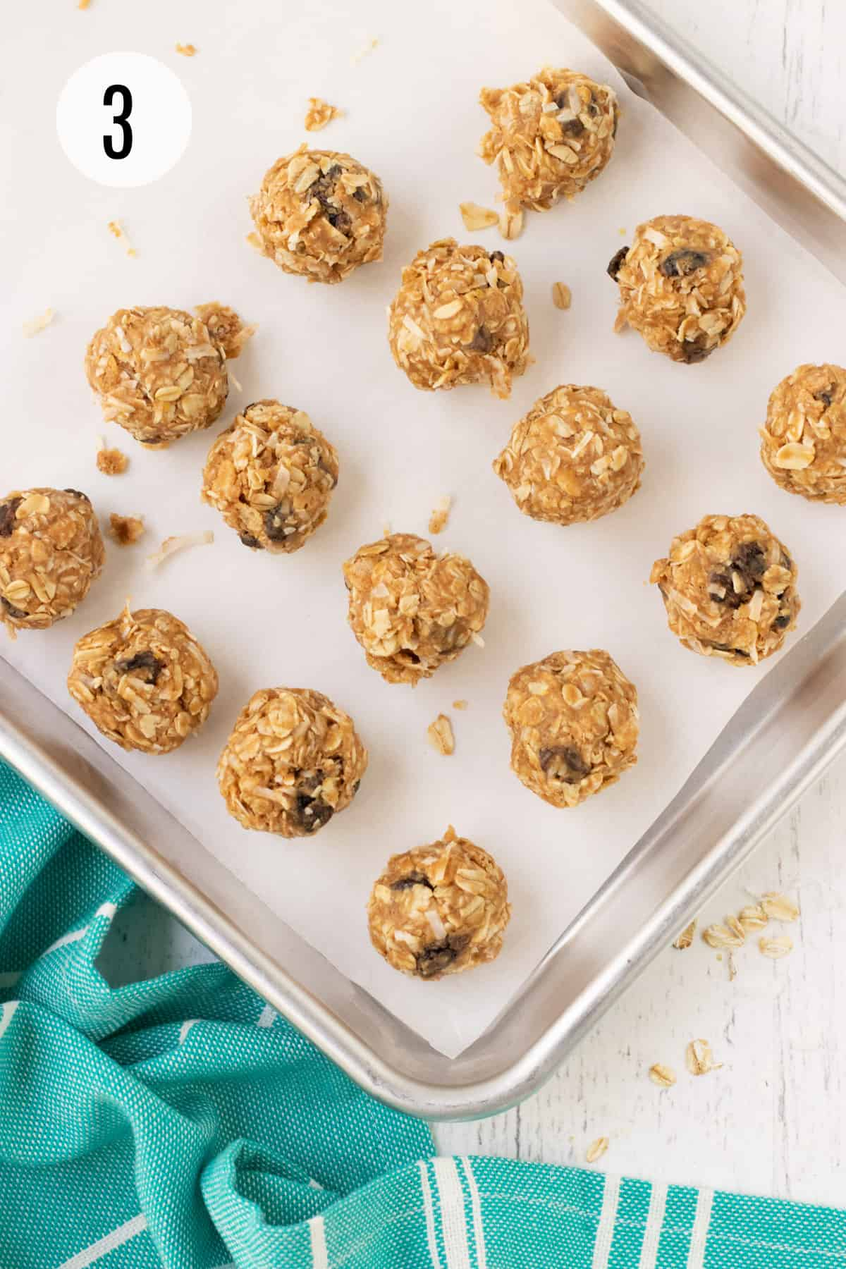 Silver baking tray lined with parchment paper and peanut butter oatmeal raisin protein balls and aqua linen in lower left corner.