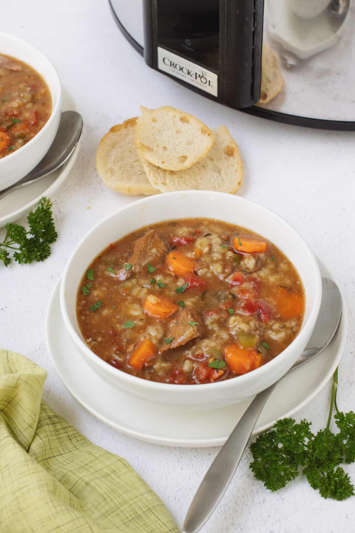 White bowl of beef and vegetable soup with spoon on plate and extra serving, slices of bread and slow cooker in upper background and parsley and green linen in lower background.