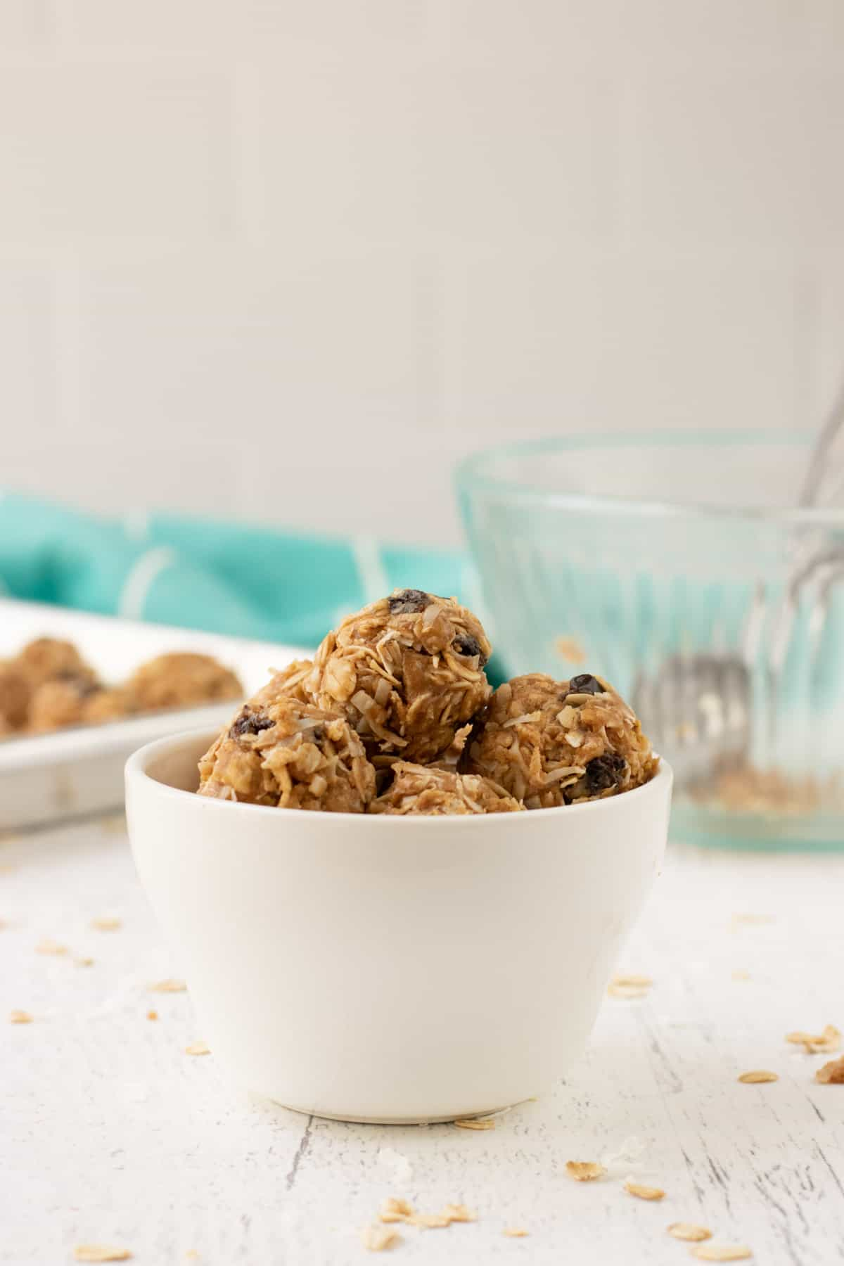 No Bake Peanut Butter Oatmeal Balls in a white bowl with tray of balls and empty ingredient bowl and aqua linen in background.