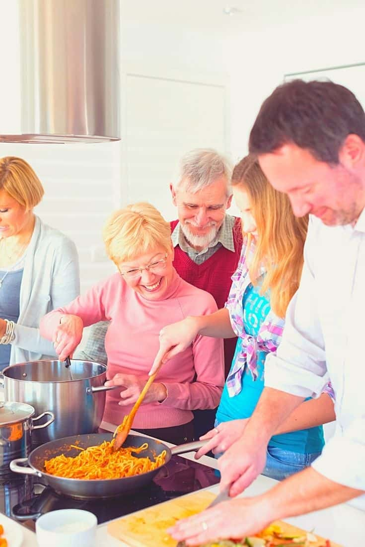 Men and women in family smiling and  cooking pasta and chopping vegetables.