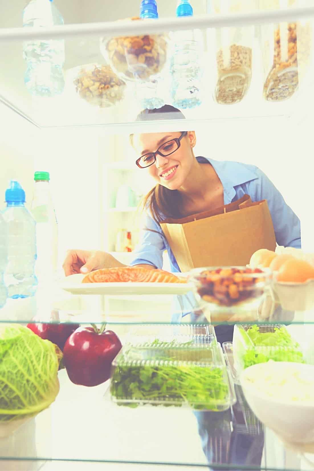 Woman unloading groceries into refrigerator with other items like lettuce, apples, fish, eggs and water bottles, etc.