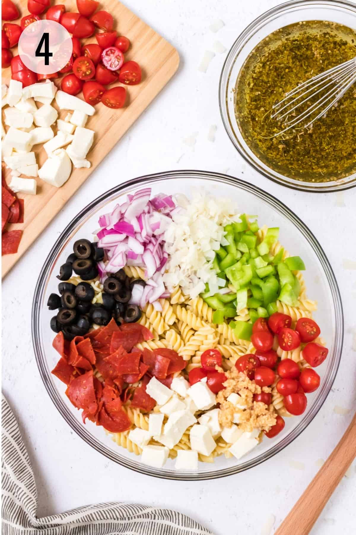 Glass bowl of ingredients for pepperoni pasta salad including fresh vegetables and smaller bowl of oil and vinegar herb dressing with cutting board of tomatoes and fresh mozzarella in upper background.