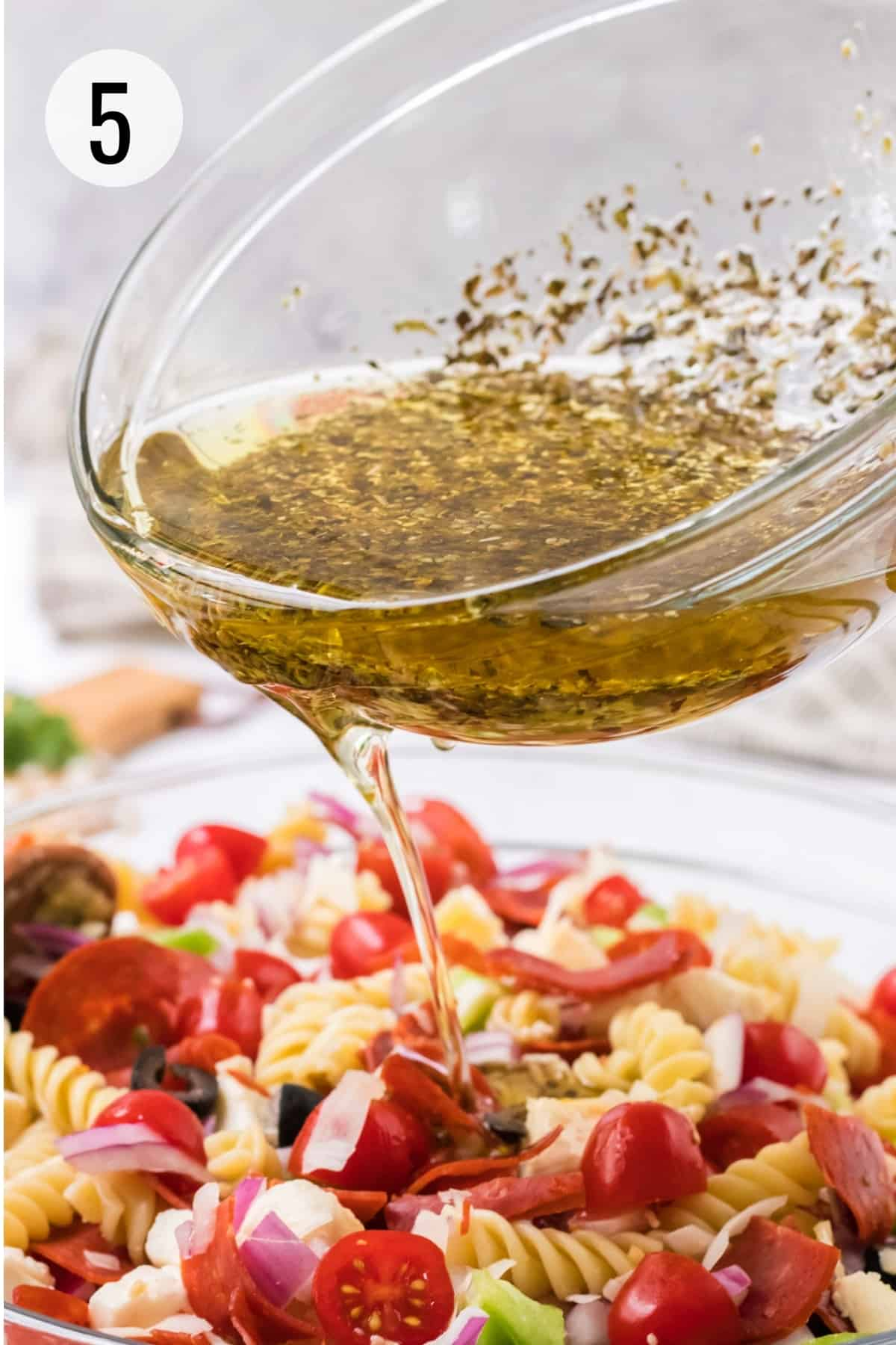 Glass bowl pouring Italian herb oil and vinegar dressing on pizza pasta salad with pepperoni.