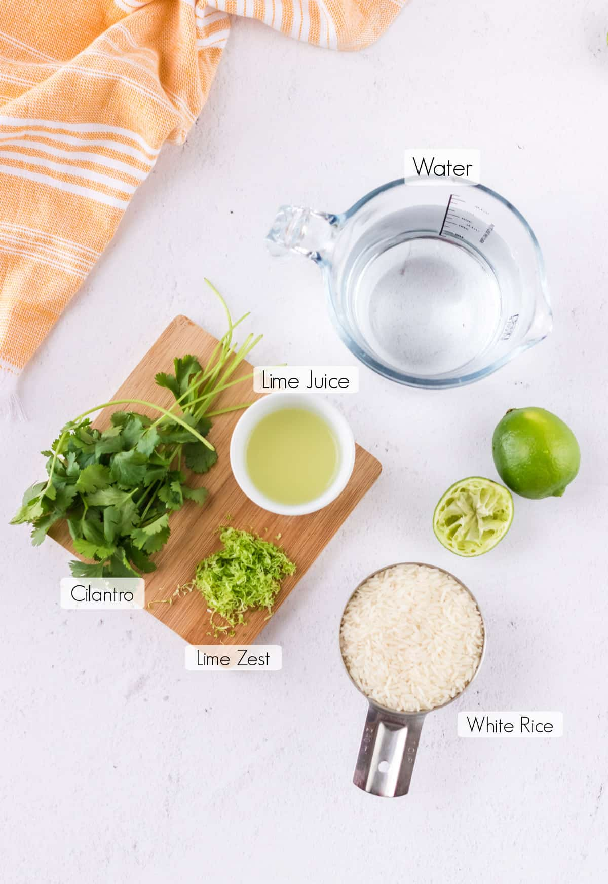Labeled ingredients to make cilantro lime rice with orange linen in upper background.
