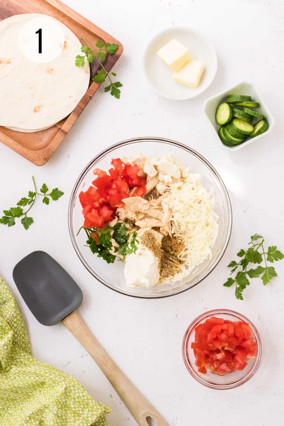 Glass bowl with cheeses, diced tomatoes, herbs and shredded chicken and small bowl of tomatoes and spatula in lower foreground and sliced cucumbers, butter and tray of tortillas in upper background.