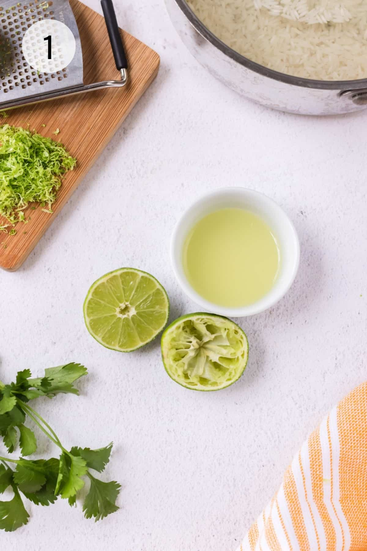 Bowl of fresh lime juice with cut limes adjacent, one squeezed and cutting board with lime zest and zester and silver pan of rice in upper background.