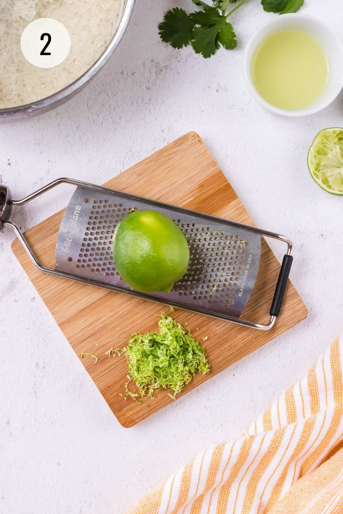 Small wooden cutting board with metal zester and lime on top with zest on board and metal pan of rice and bowl of lime juice and cilantro sprig in upper background