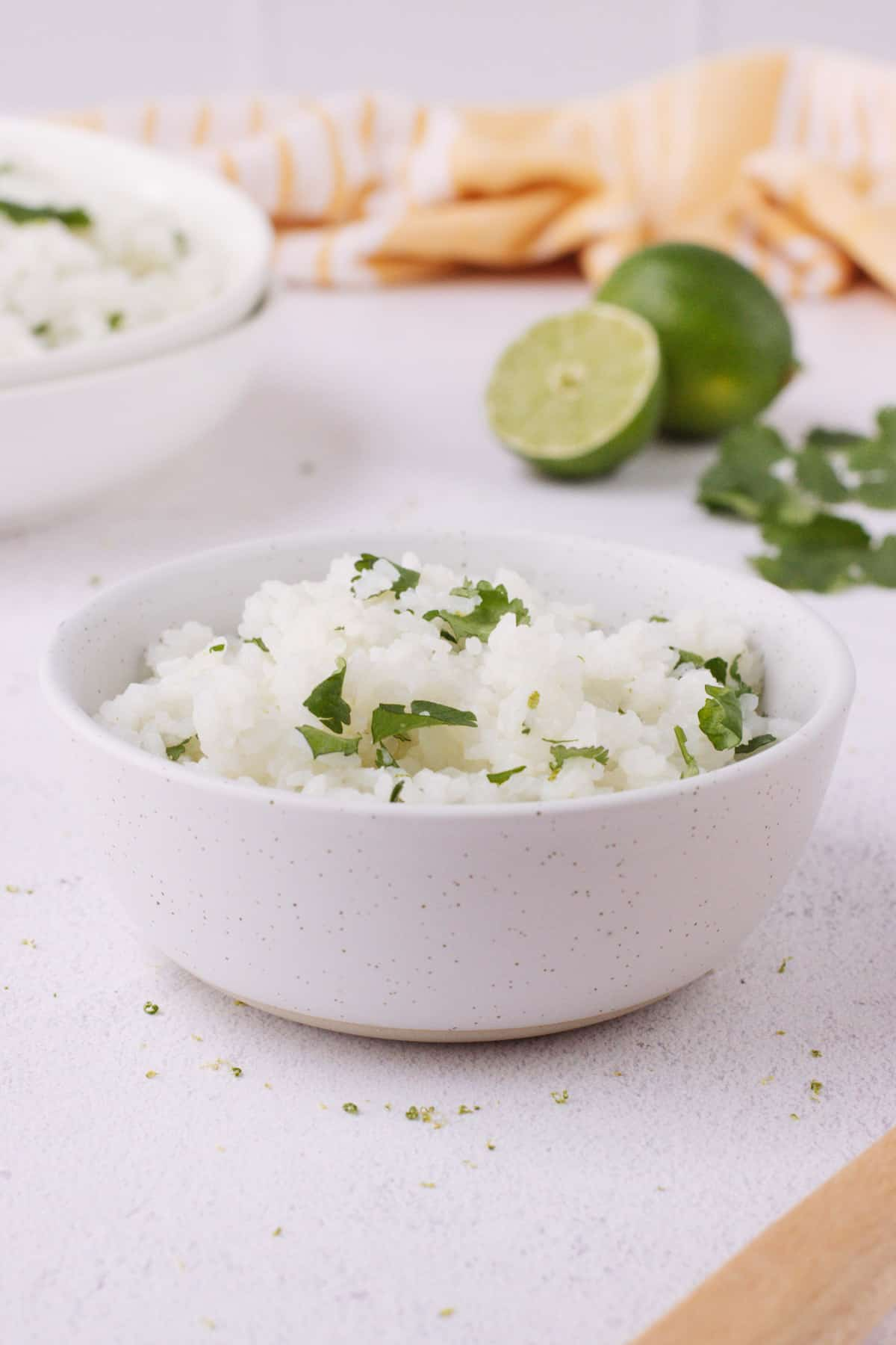 White bowl with white rice and chopped cilantro with cut and whole lime and bowl full of more rice in background with orange linen.