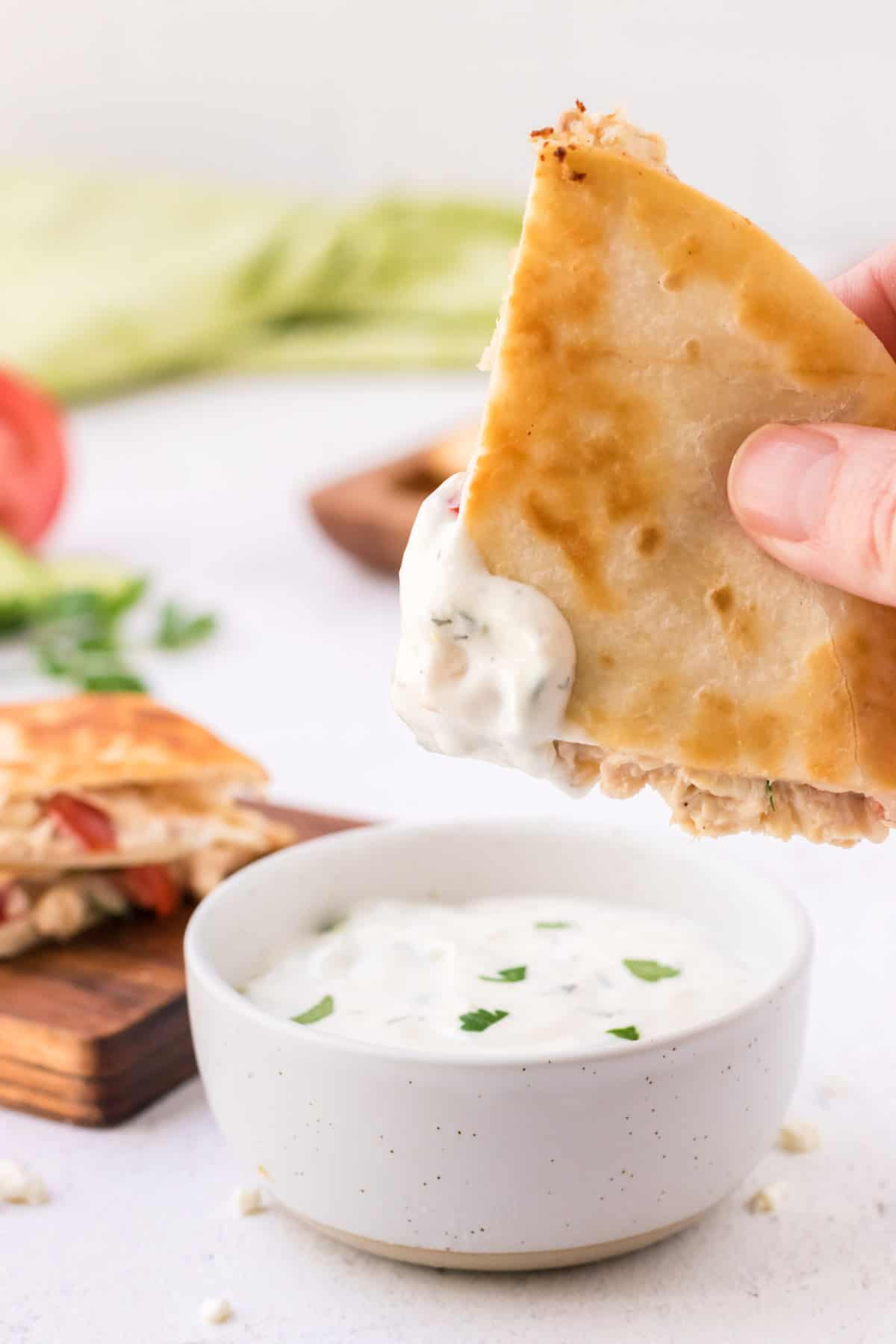Triangle of Greek quesadilla being dipped in tzatziki sauce and cutting board of stacked quesadillas and green linen in background.