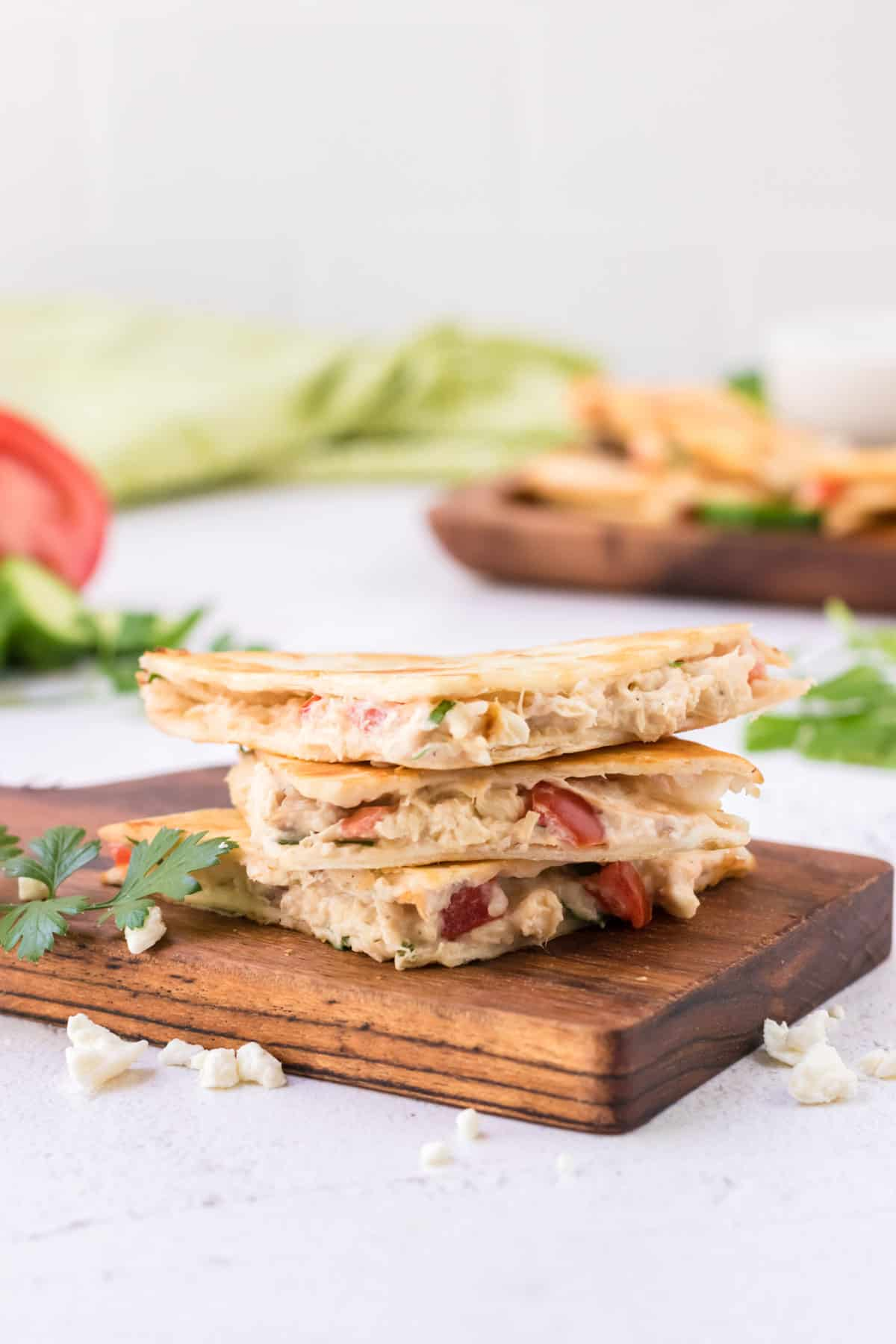 Wooden cutting board with stack of Greek quesadillas and tray of more quesadillas and green linen in background.