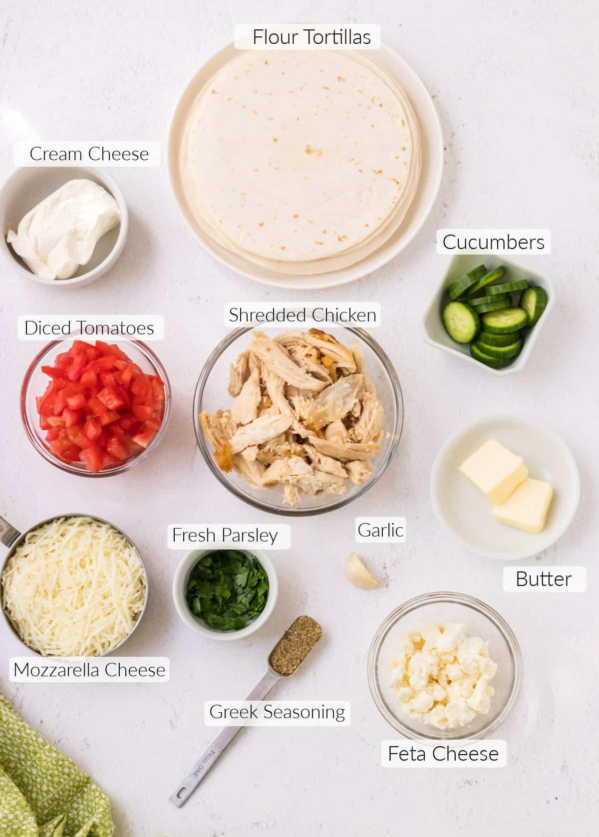 Labeled ingredients in bowls to make Greek quesadillas.
