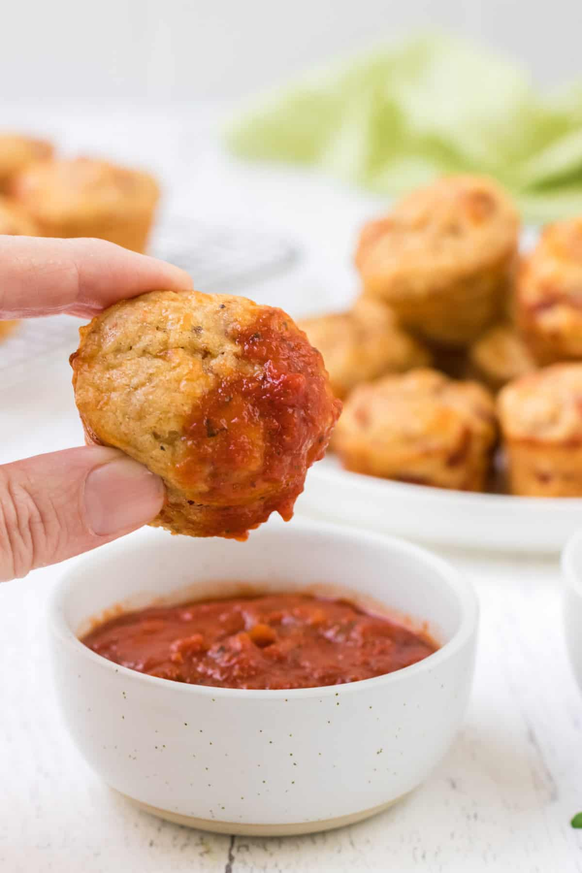 Hand holding a mini pizza muffin dipped in a white bowl of marinara sauce with plate of muffins in background.