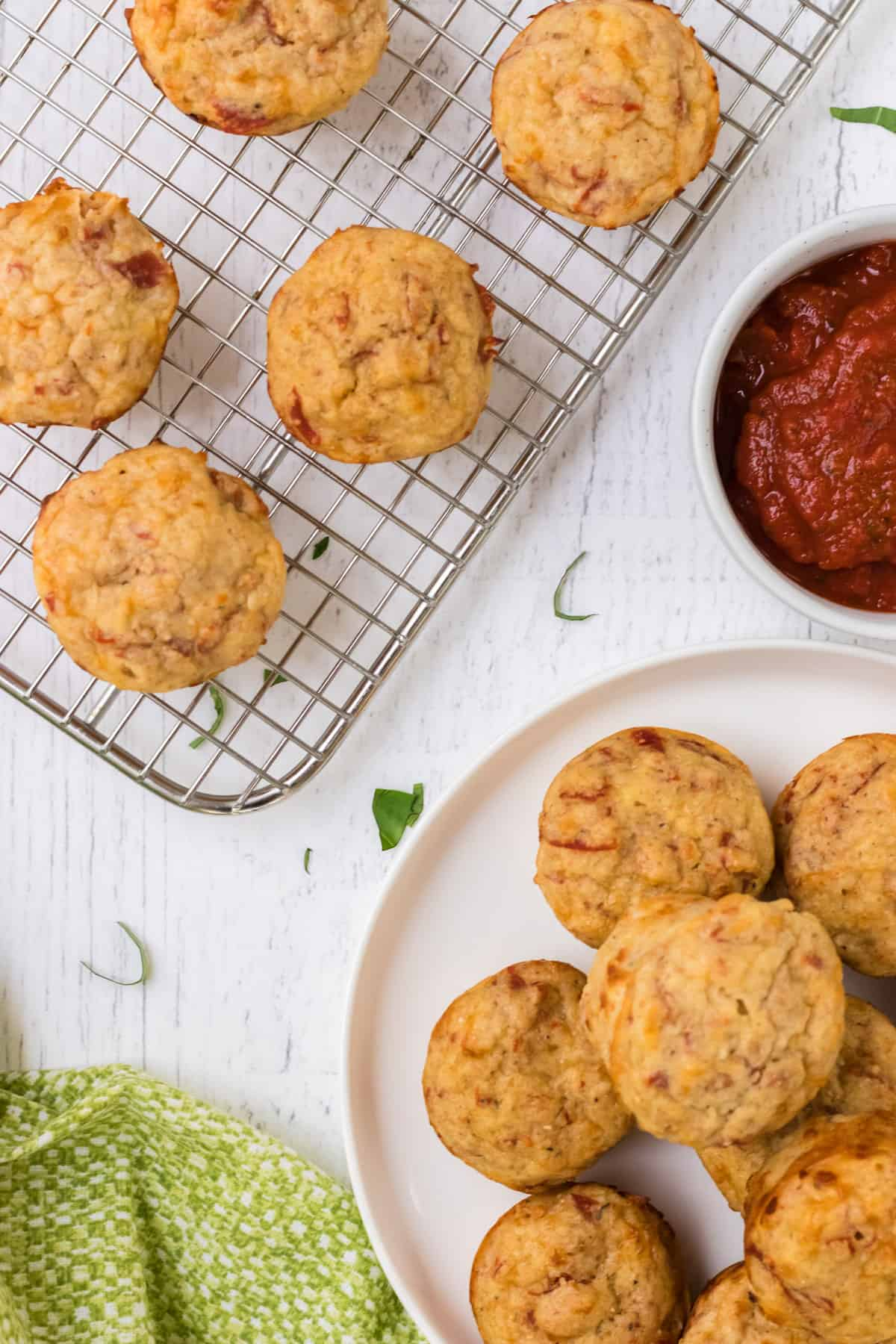 Silver cooling rack with muffins and white plate of pizza muffins with bowl of marinara sauce in upper background and green linen in lower foreground.