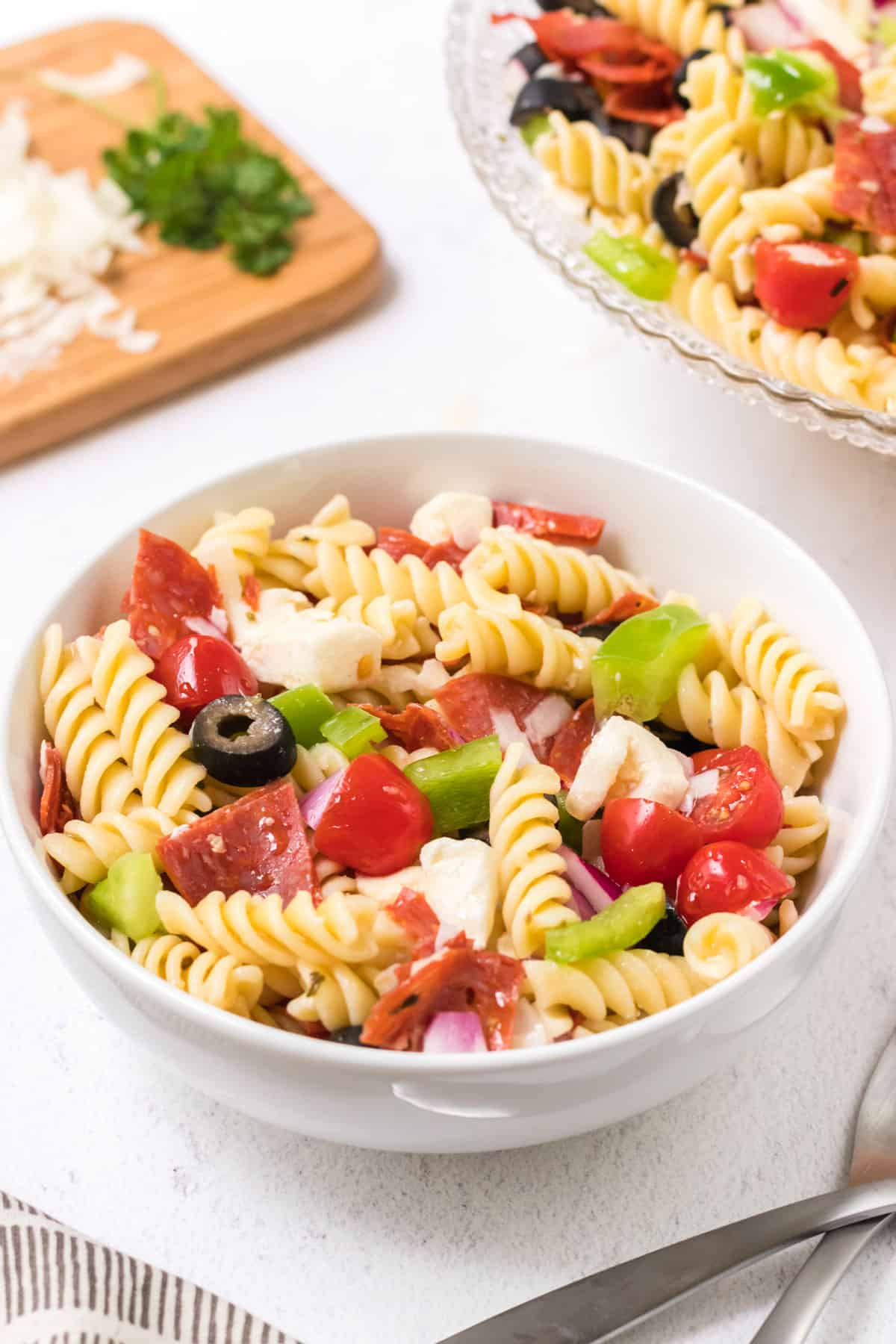 White bowl with Italian pasta salad with tomatoes, green bell peppers, fresh mozzarella, pepperoni, black olives and purple onion with cutting board and large bowl of pasta salad in upper background.