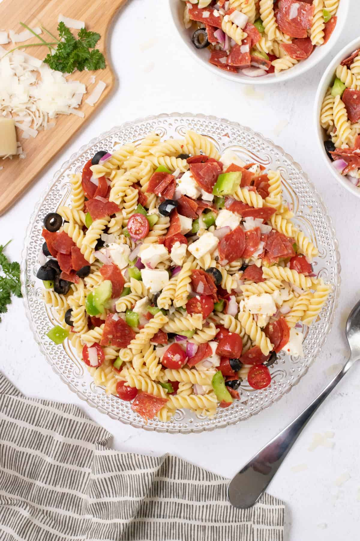 Large glass bowl of Italian pasta salad with pepperoni and fresh vegetables with cutting board of shredded cheese and smaller bowls of pasta salad in upper background.