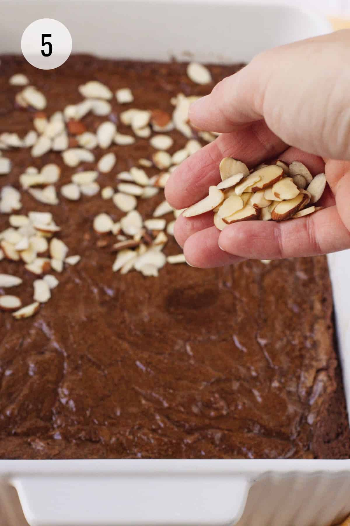 Hand sprinkling sliced almonds on partially baked pan of Mexican brownies.