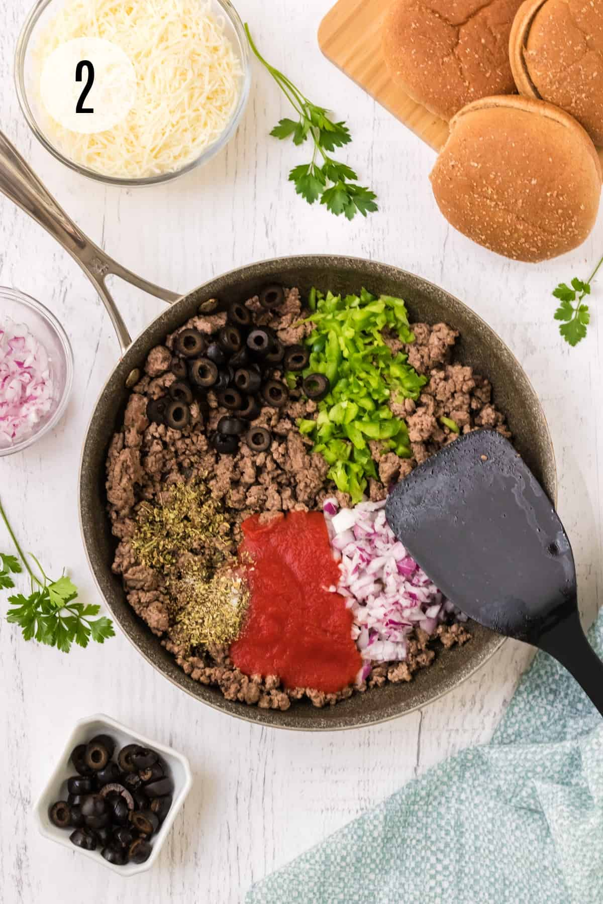 Skillet of ingredients for Italian Sloppy Joes like ground beef, onions, tomato sauce, and olives with small bowl of olives in lower left, chopped onions and bun in upper photo and blue linen in lower right.