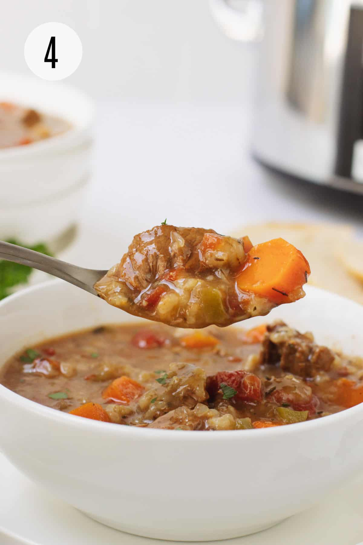 White bowl with Crockpot Vegetable Beef Barley Soup and also on spoon with carrot and beef with silver and black slow cooker and additional soup in upper background.